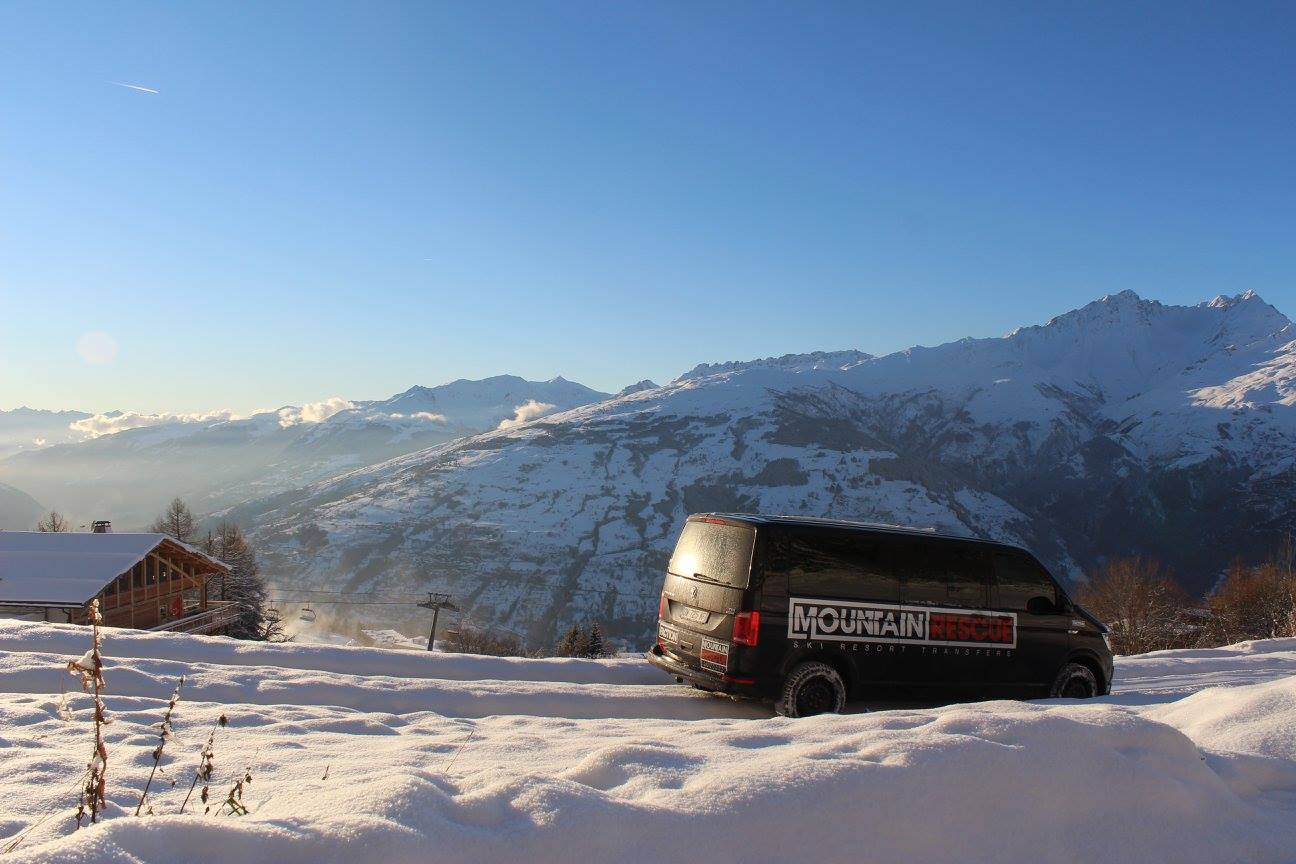 Minibus doing down snow covered road with mountains in background