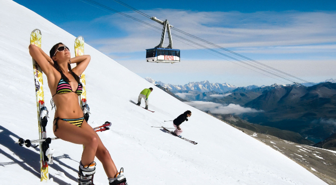 Woman sitting in a bikini on a seat made with her skis and sticks