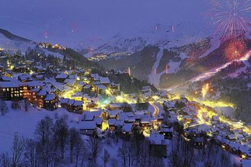 Night time view of ski resort chalets and exploding fireworks