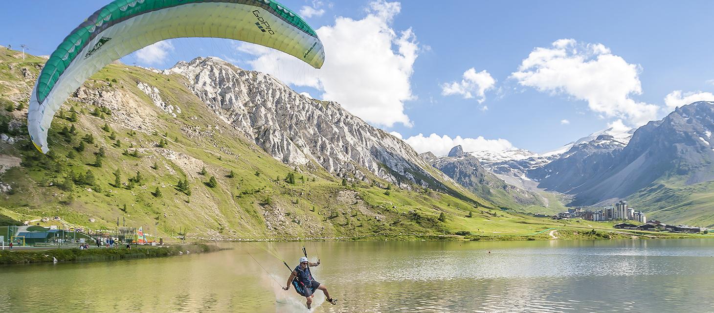 Paraglider landing on lake in Tignes