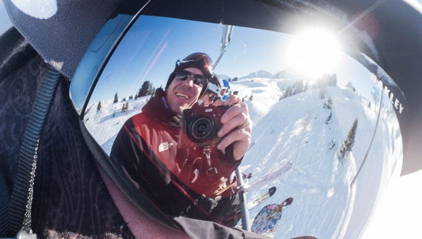 Skier taking a photo of himself in friends goggles